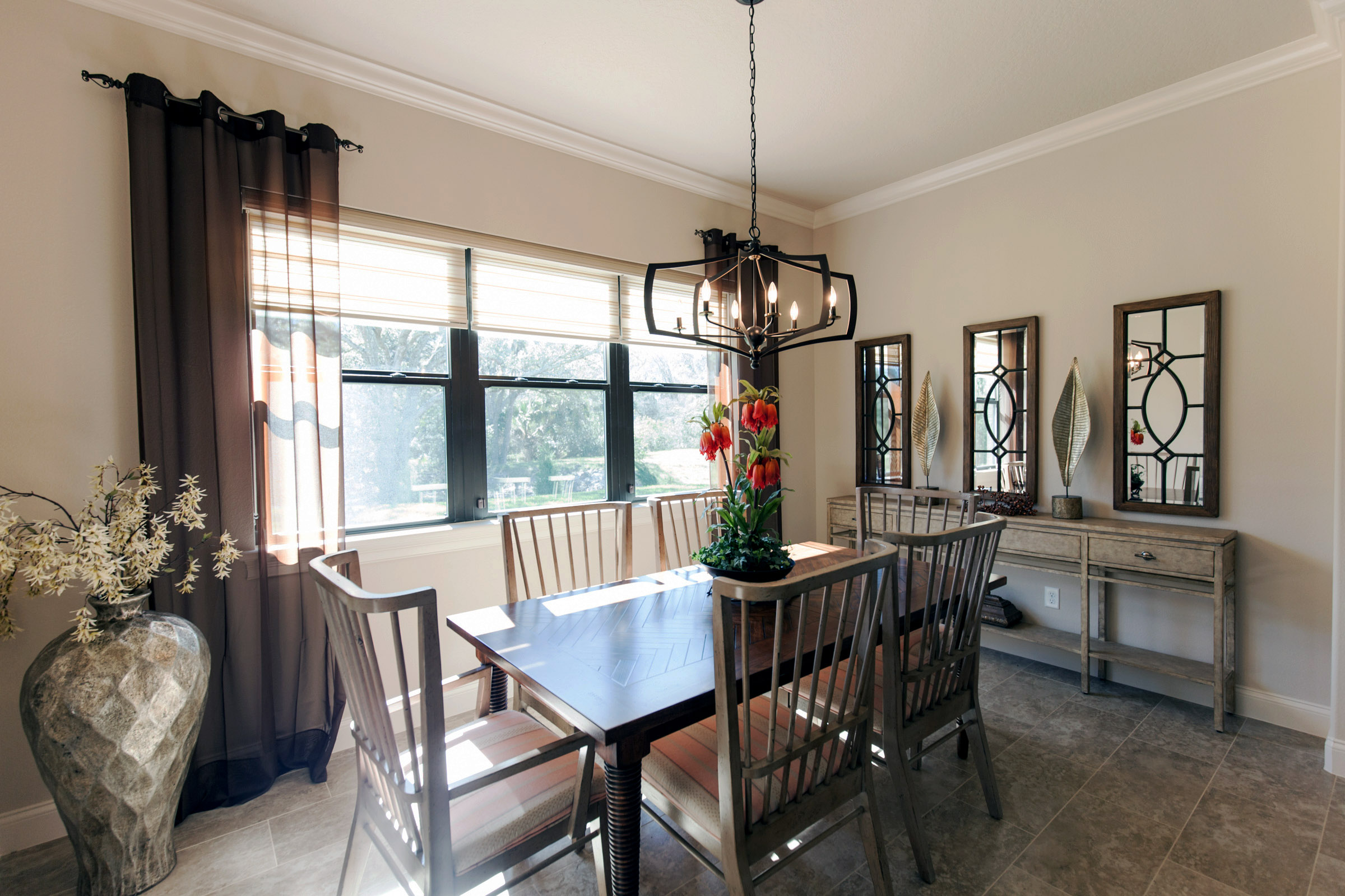 Dining area with wood table and chairs and large open windows