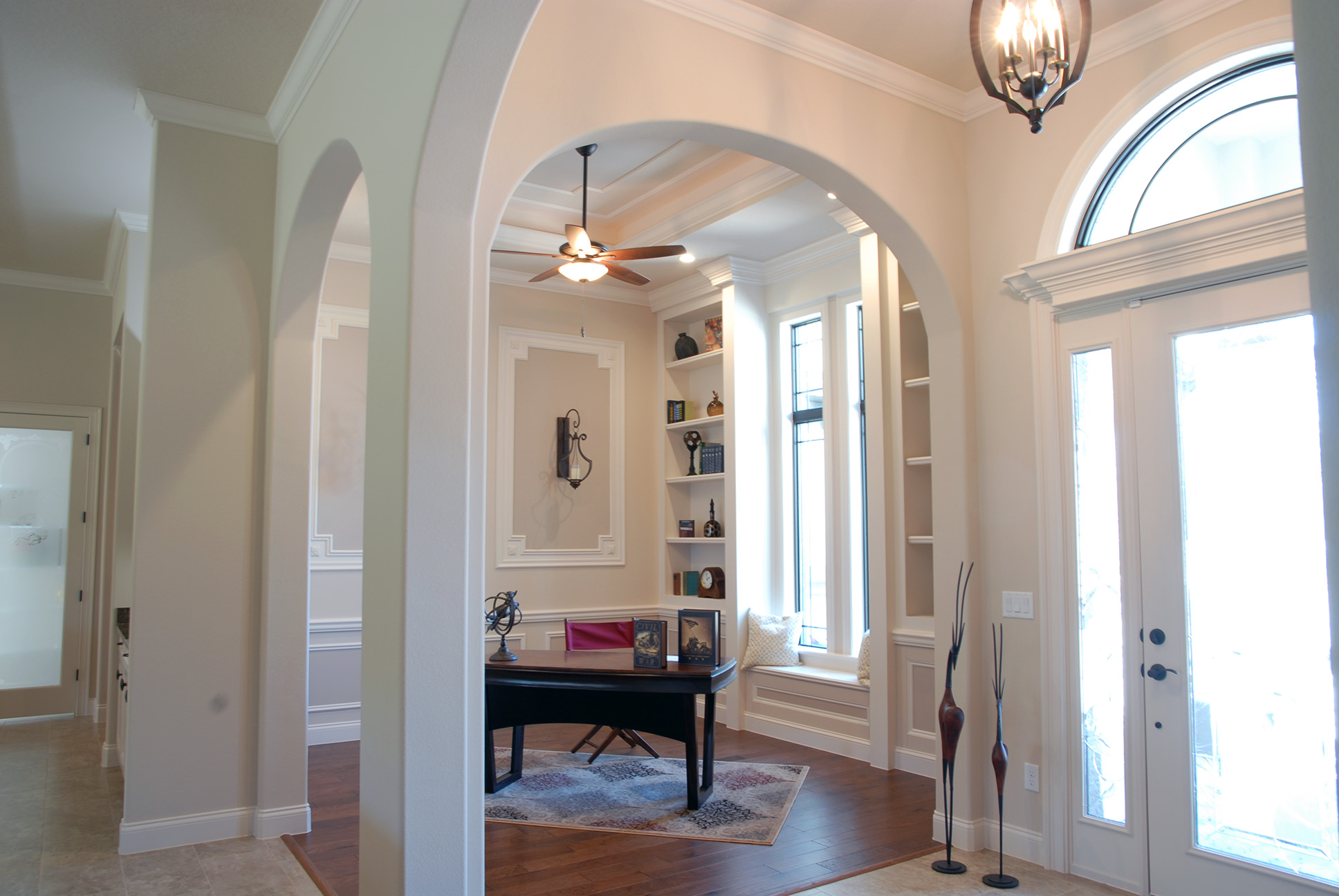 Corner office area next to front door with arch details throughout