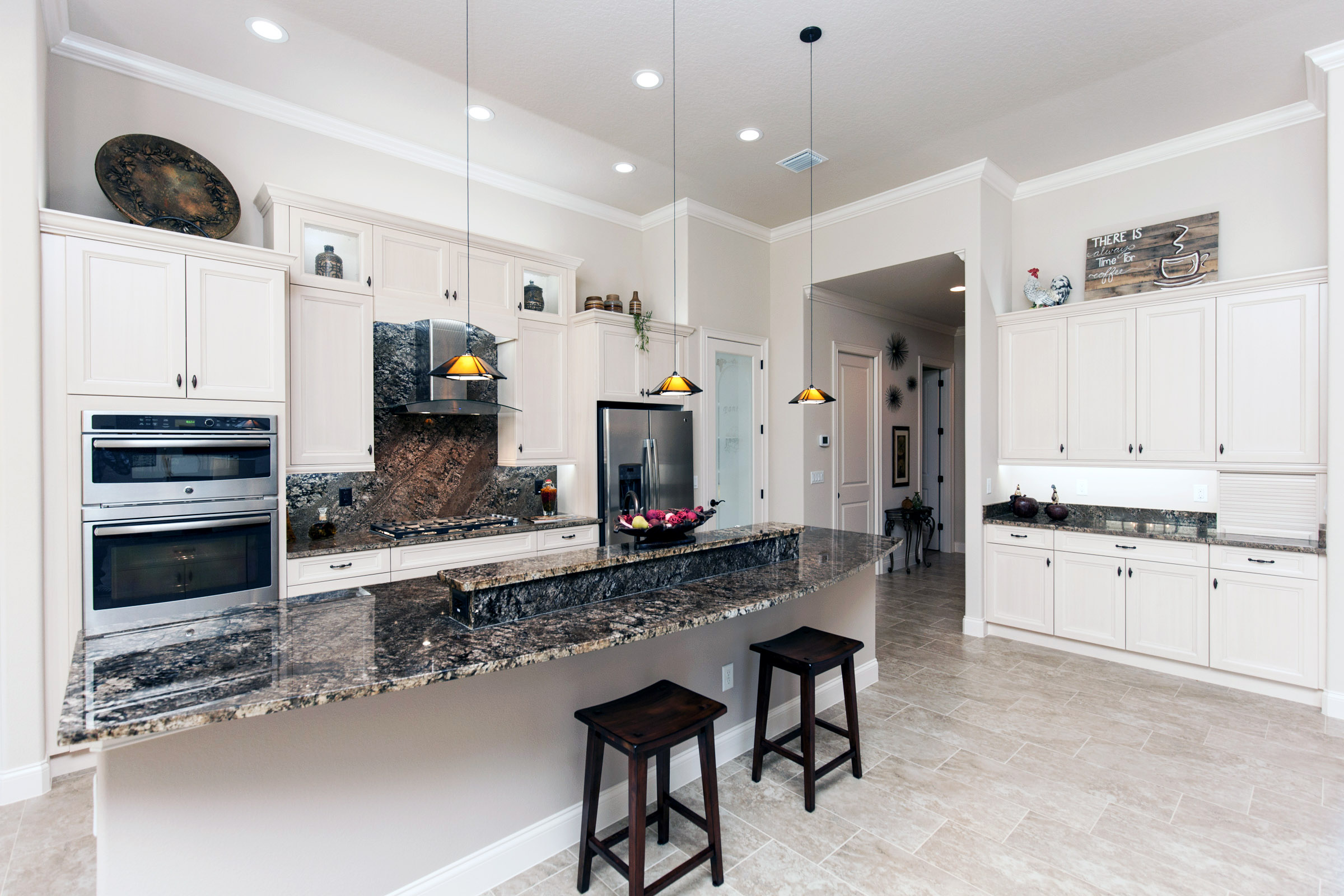 Kitchen with long bar and white cabinets