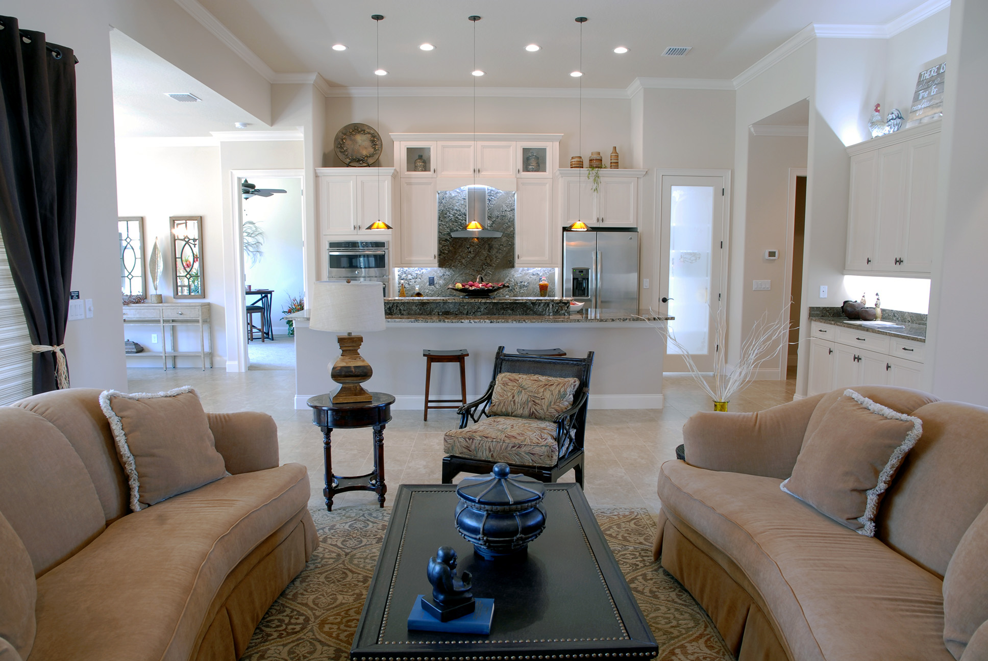 Open kitchen and living area with matching brown couches
