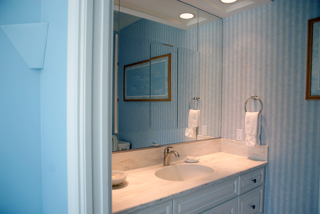 Light blue striped wall paper and single vanity with chrome details.
