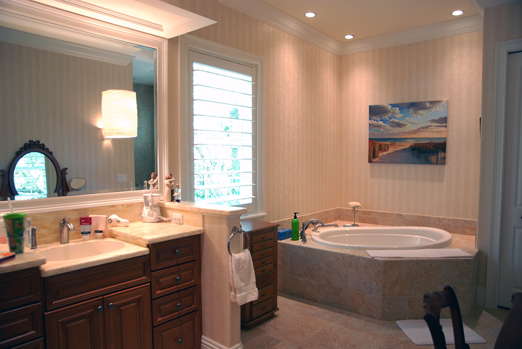 Master bathroom with large corner tub and dark wood cabinets