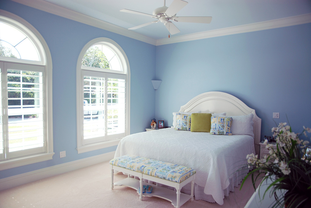 Light blue bedroom with large arched windows and queen size bed
