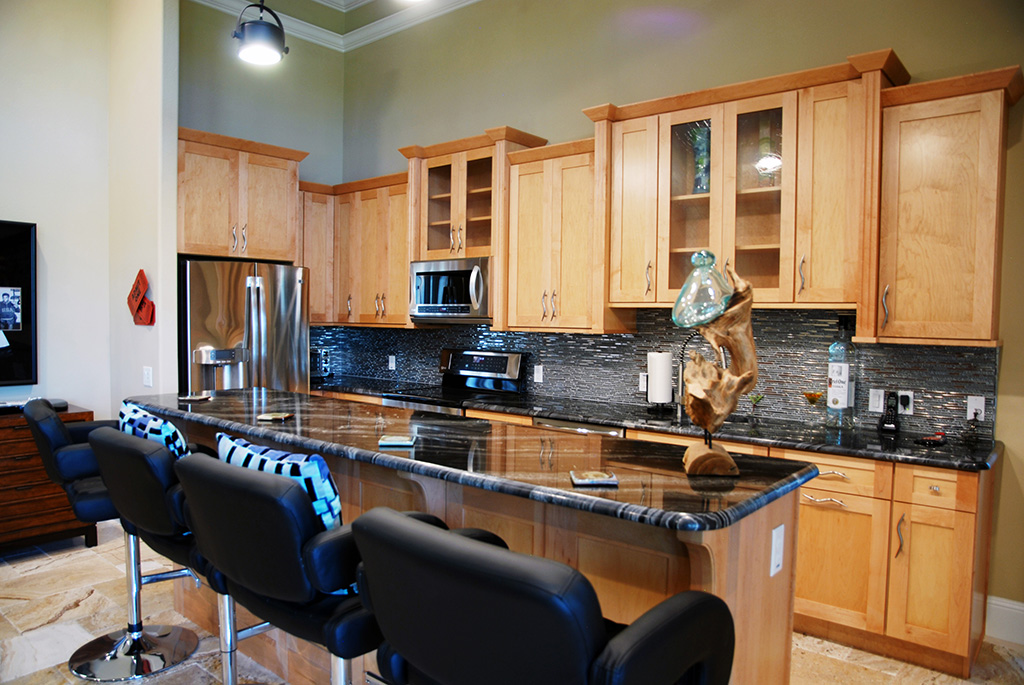 Custom build kitchen with light wood cabinets and dark back splash