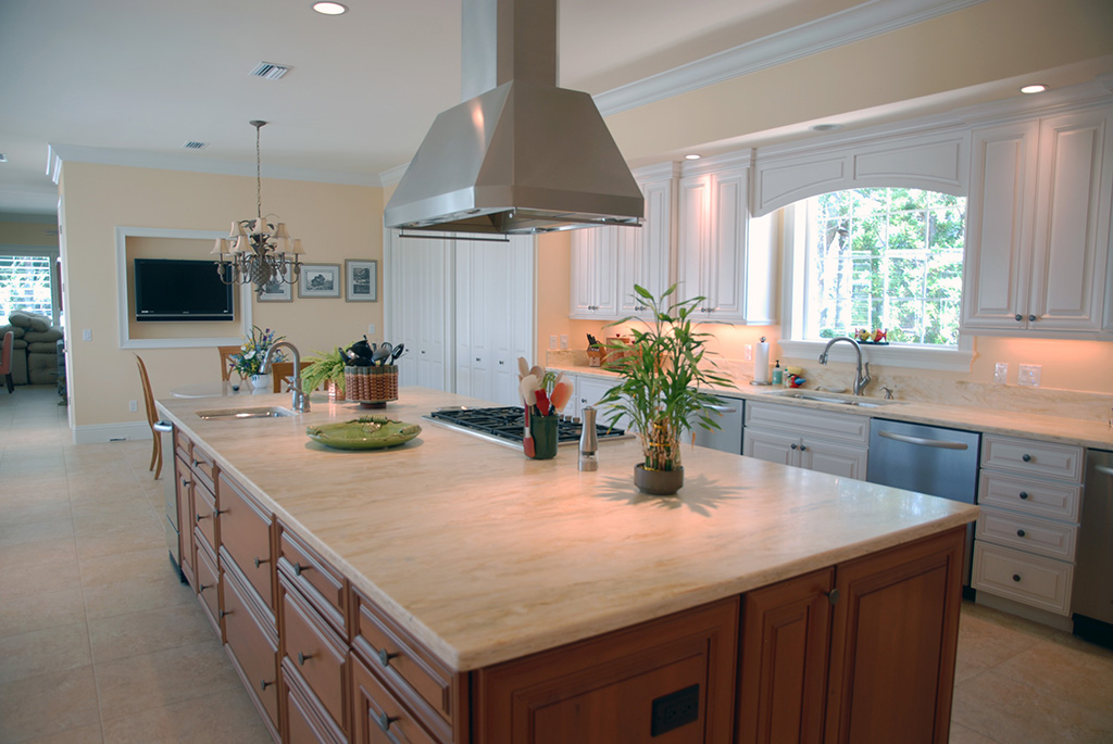 Full kitchen view featuring island with brown cabinets and stainless steel appliances