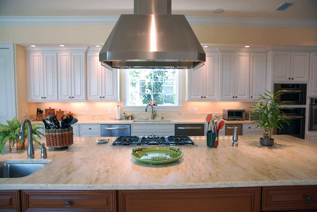 Large marble kitchen island and white custom cabinets in an open kitchen