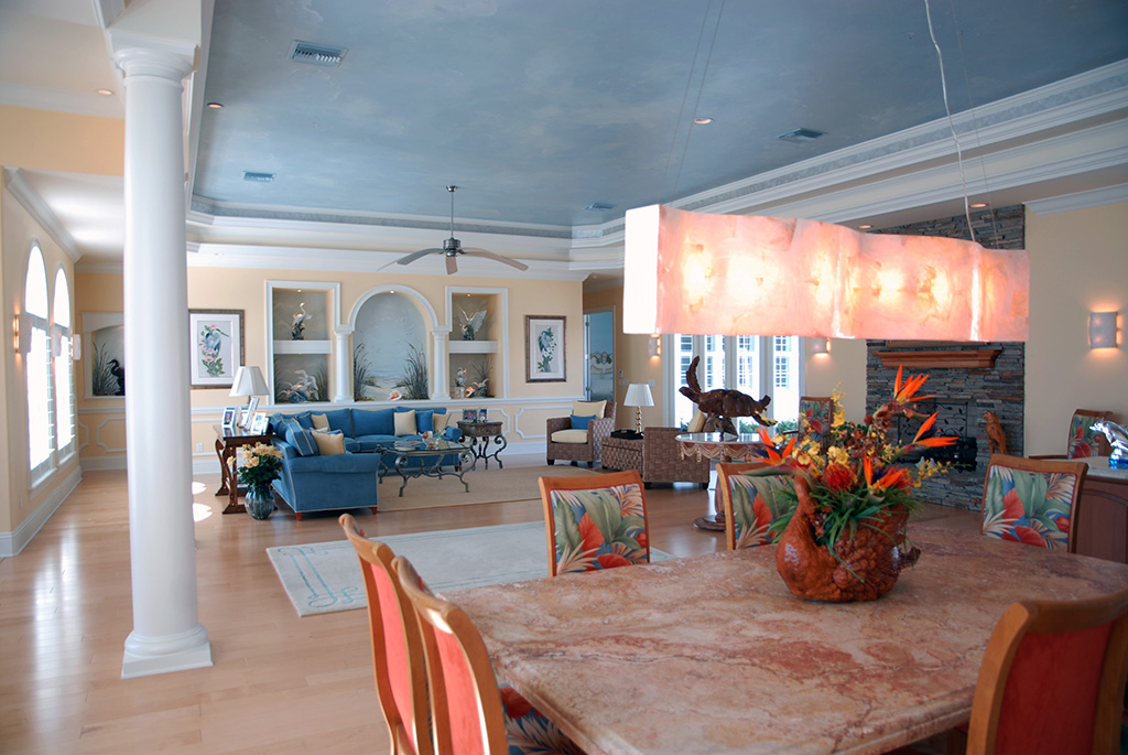 Large open concept including dining table and view of large living room and light blue pained ceiling