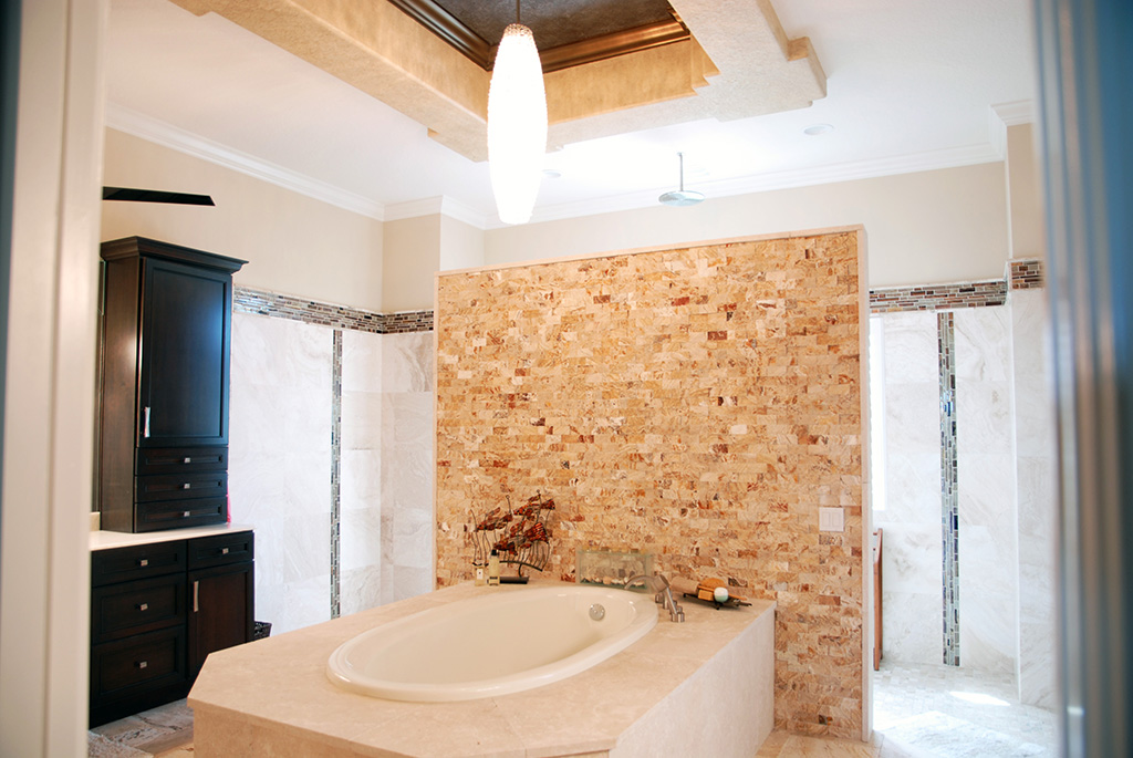 Large bathtub in master bathroom with tile wall