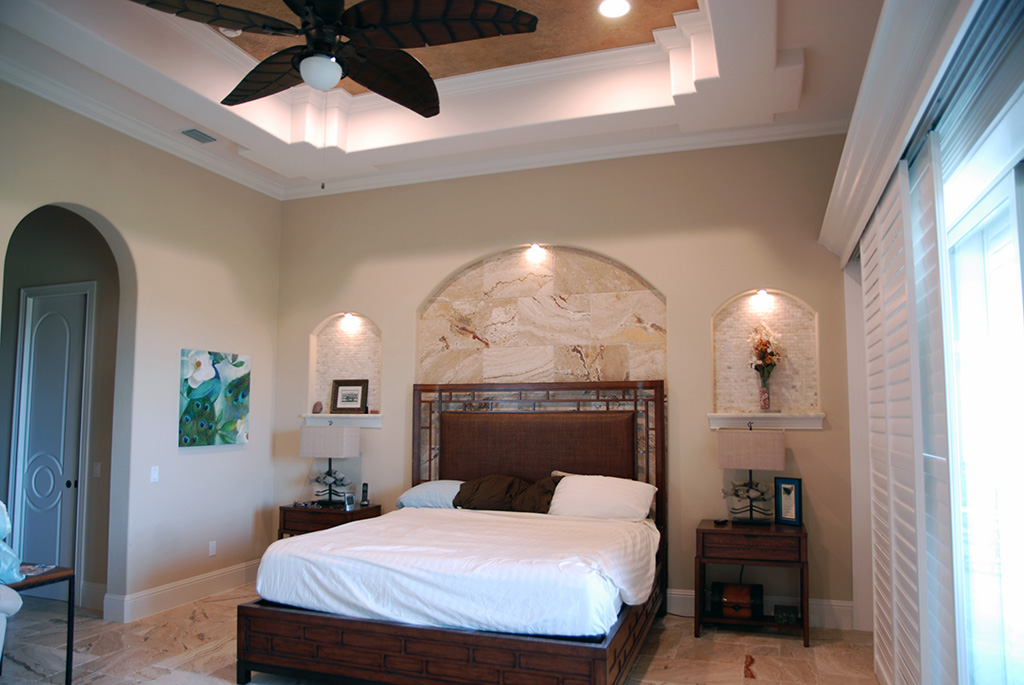Bedroom with large windows, arch built in details in wall and queen size bed