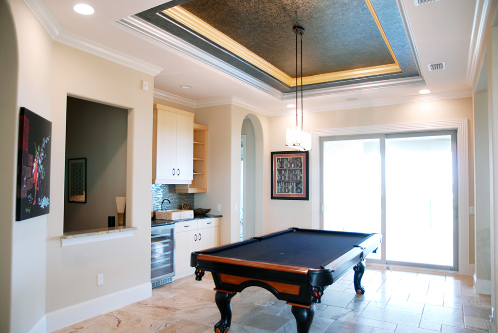 Pool table in game room with large sliding glass doors