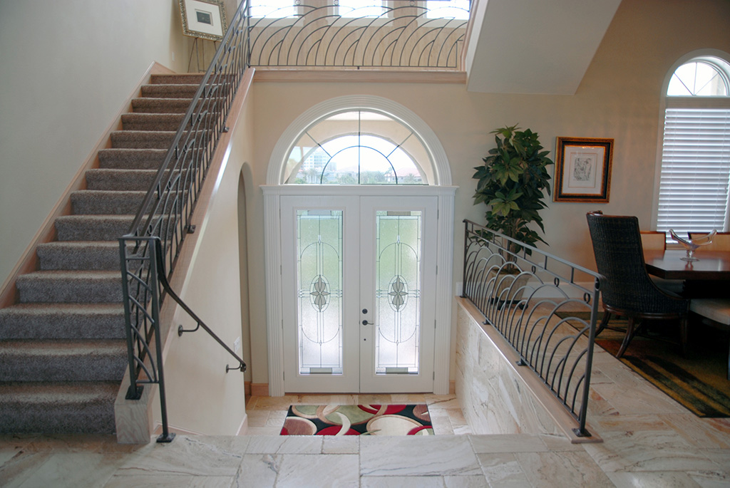 French doors with arch detail leading into custom home