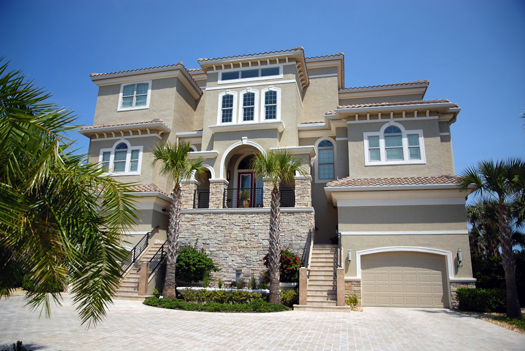 Front of home with lush palm trees and light brown exterior with white trim