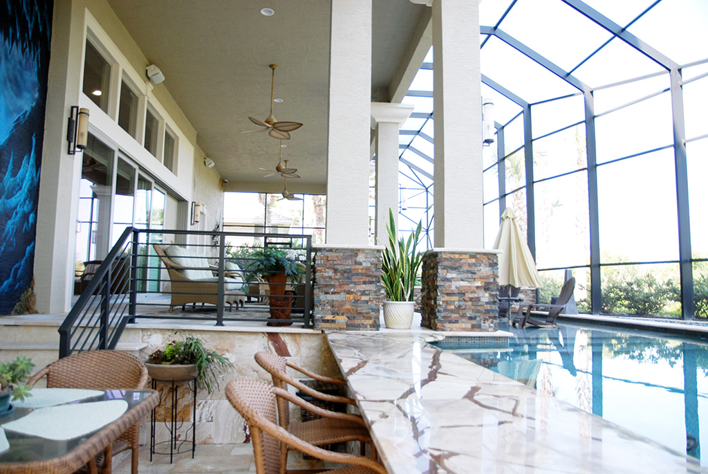 Two level outdoor living area with indoor pool and living furniture