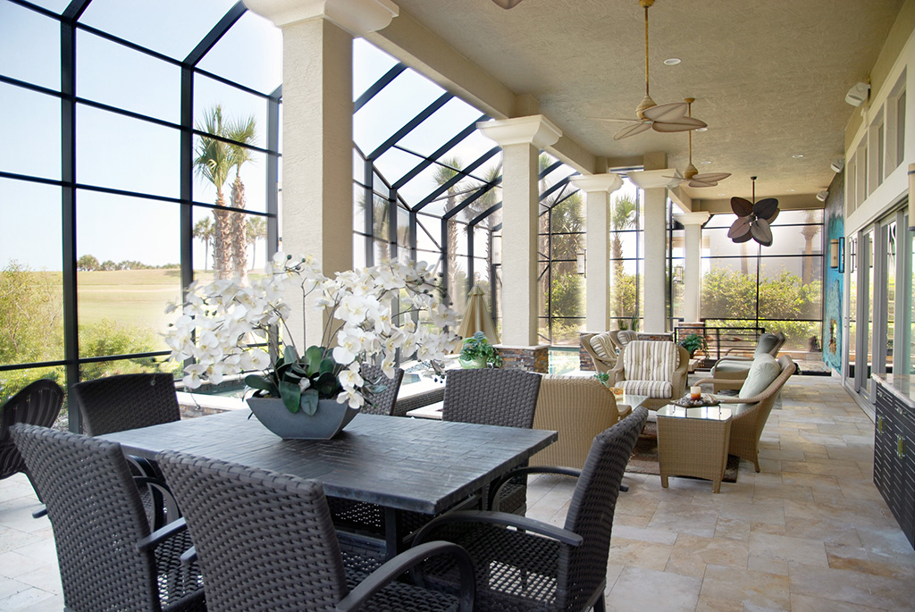 Floor to ceiling windows with decorative columns and outdoor living furniture