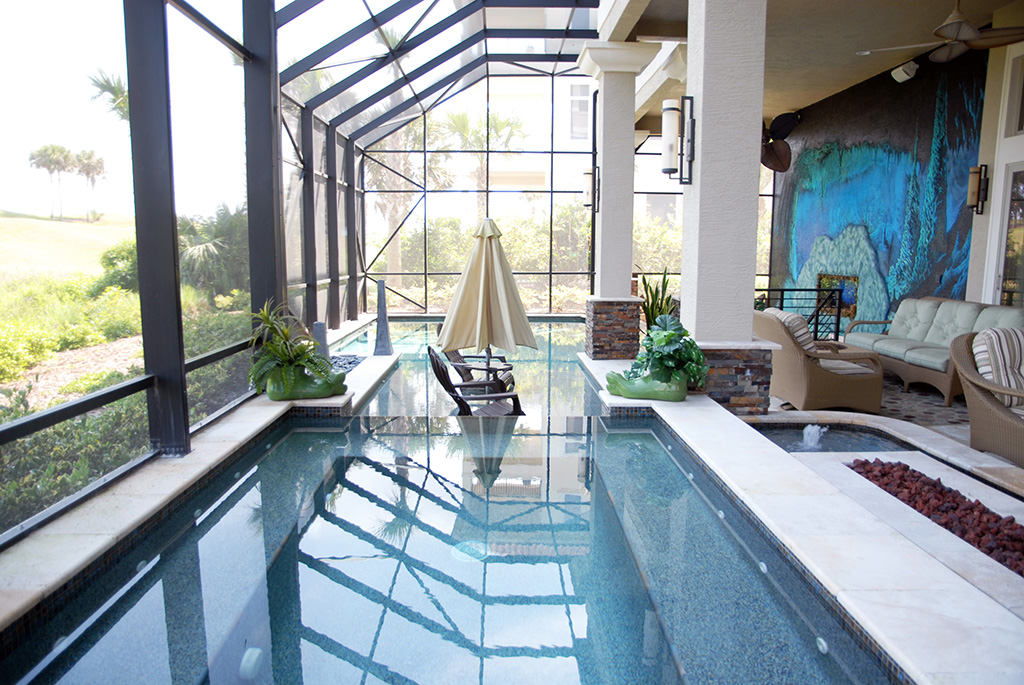 Beautiful indoor pool with outdoor furniture and large wall mural and ceiling fans