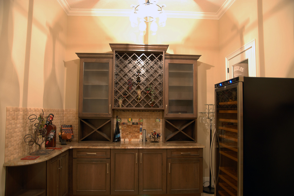 Dark wood built in bar with wine cooler.