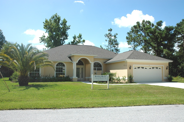 Front view of custom built home with two car garage and arched windows, door and entryway