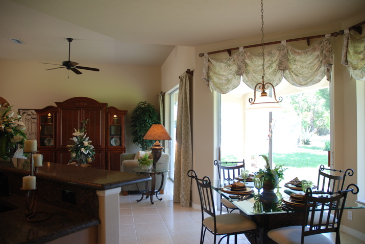 Dining room with floor to ceiling windows in a custom home build open concept floor plan
