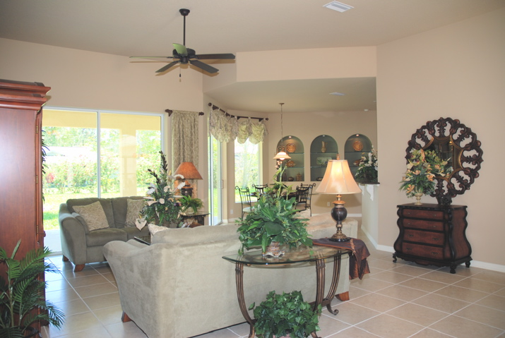 Living room with light tile and large windows overlooking the lanai