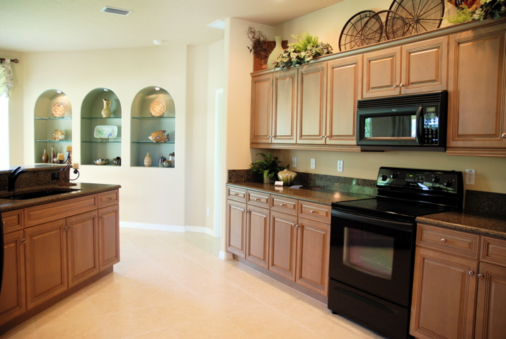 Beautiful wood kitchen cabinets with black appliances.