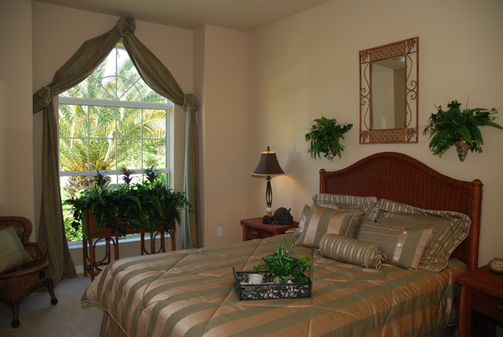 Master bedroom furnished with plants and large window