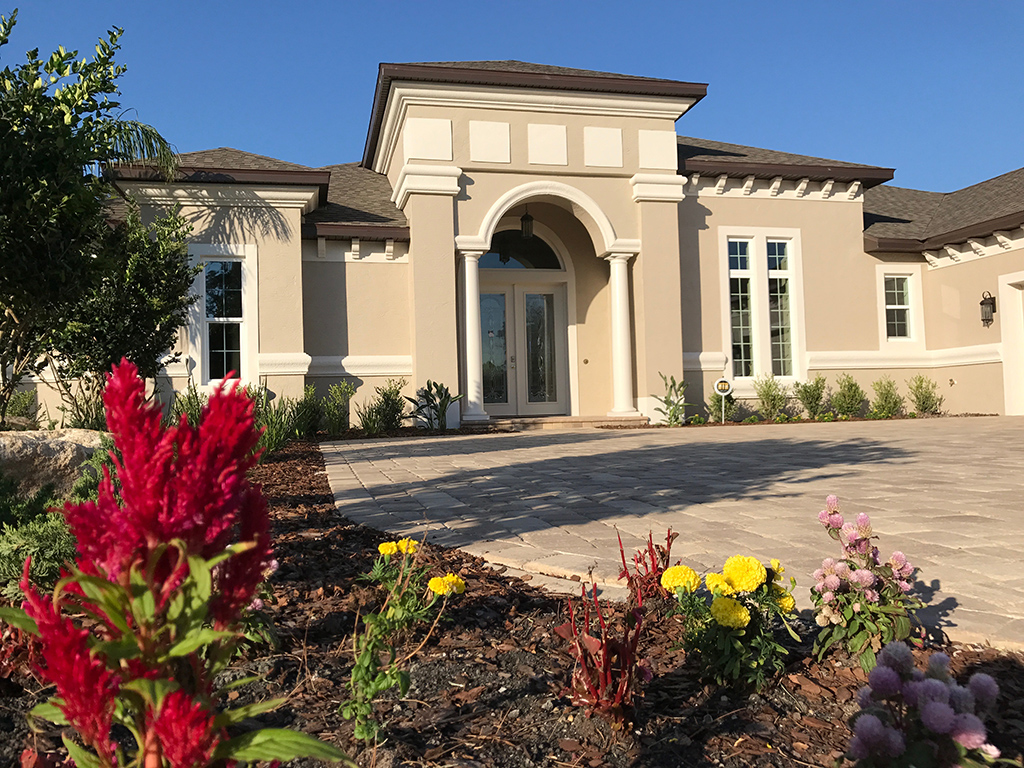 Custom home model with yellow and red landscaping