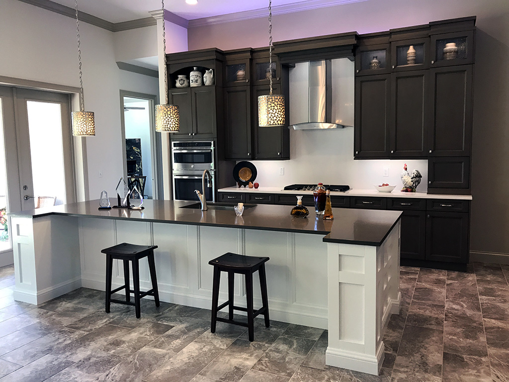 Custom home model kitchen with large kitchen island with pendant lights.