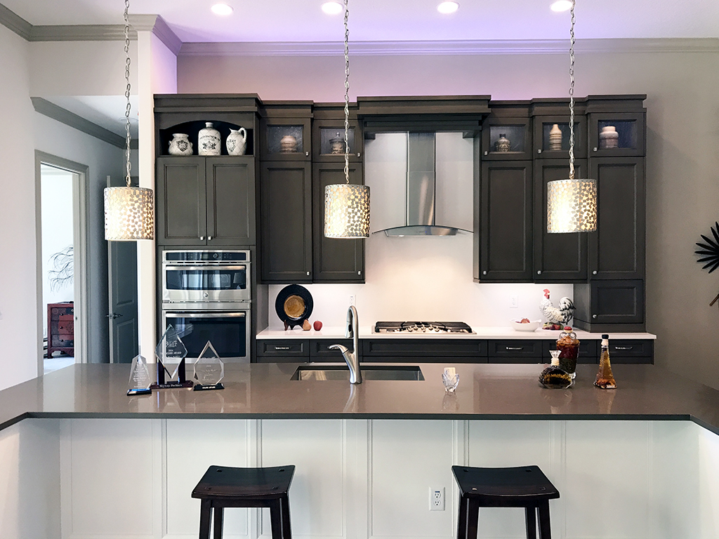 Dark colored kitchen cabinets with a stainless oven hood and kitchen island