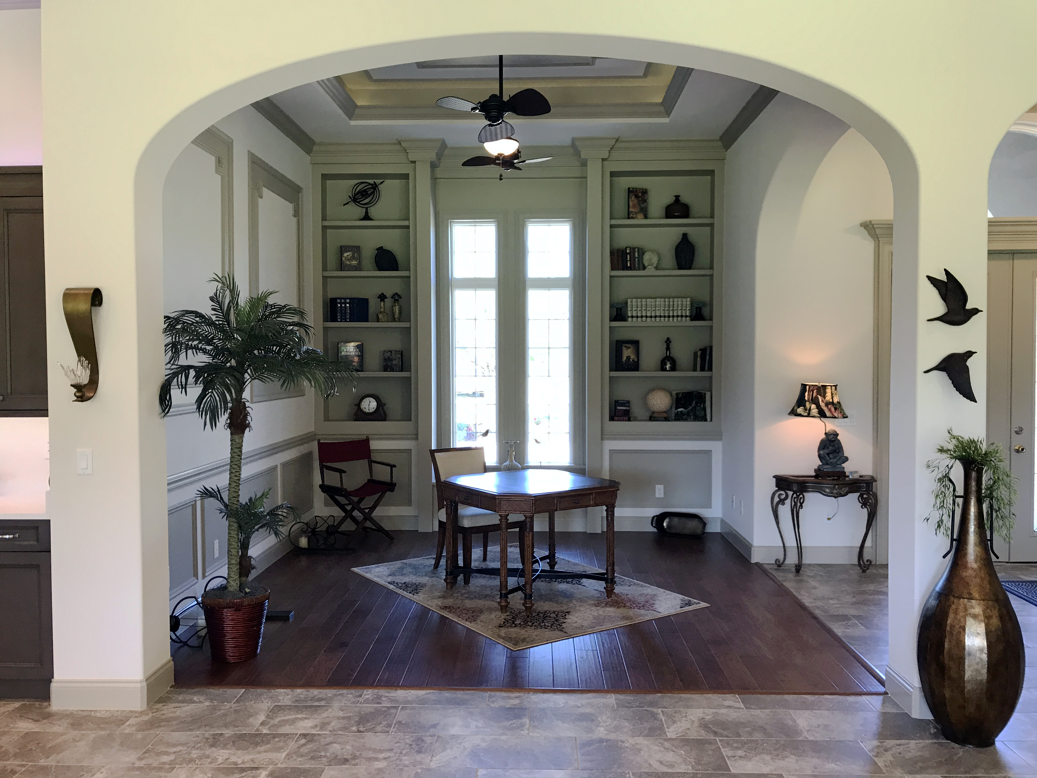 custom arched entry way to study with built in shelving and unique ceiling fan