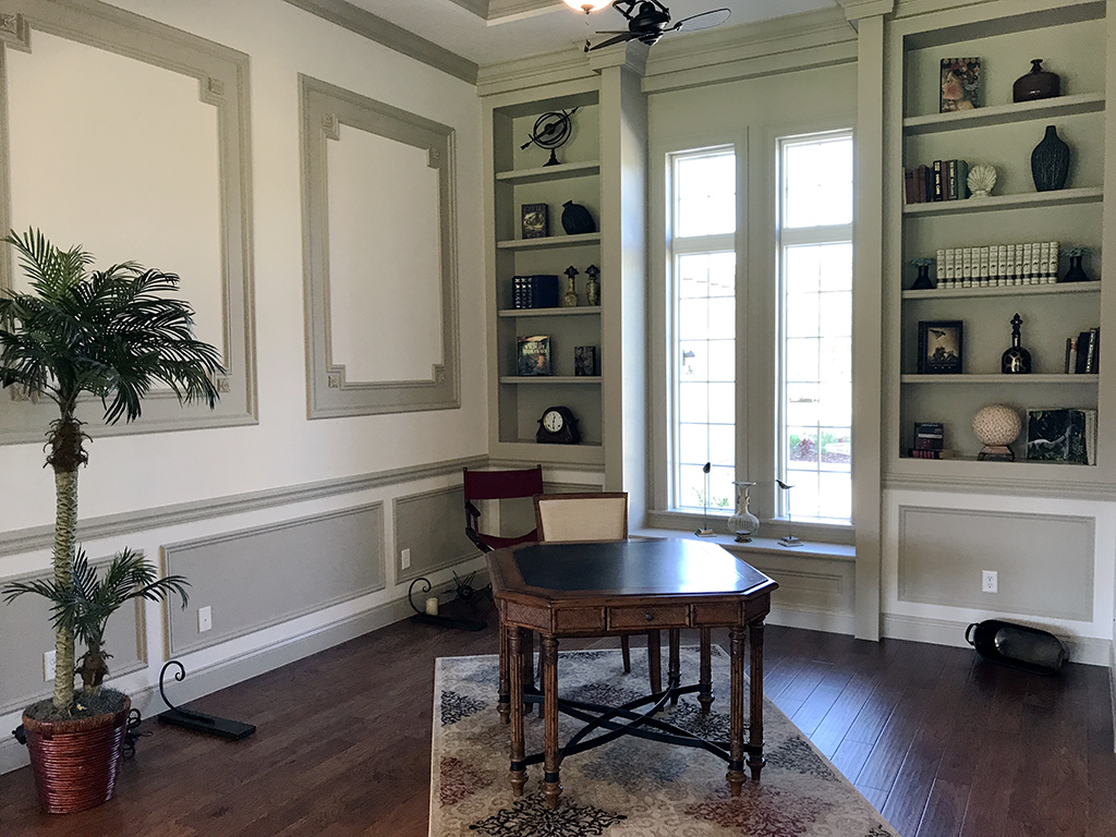 Corner study with built in shelving and tall windows