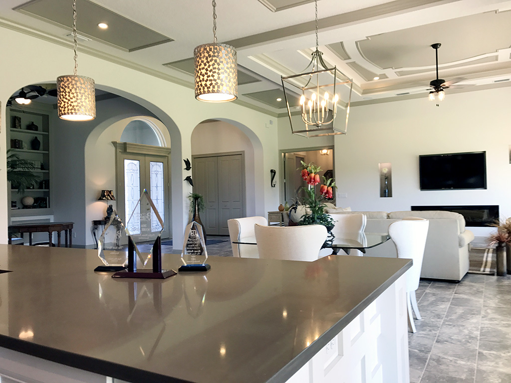Kitchen and living room with drop pendant lighting, chandelier, and ceiling fan.
