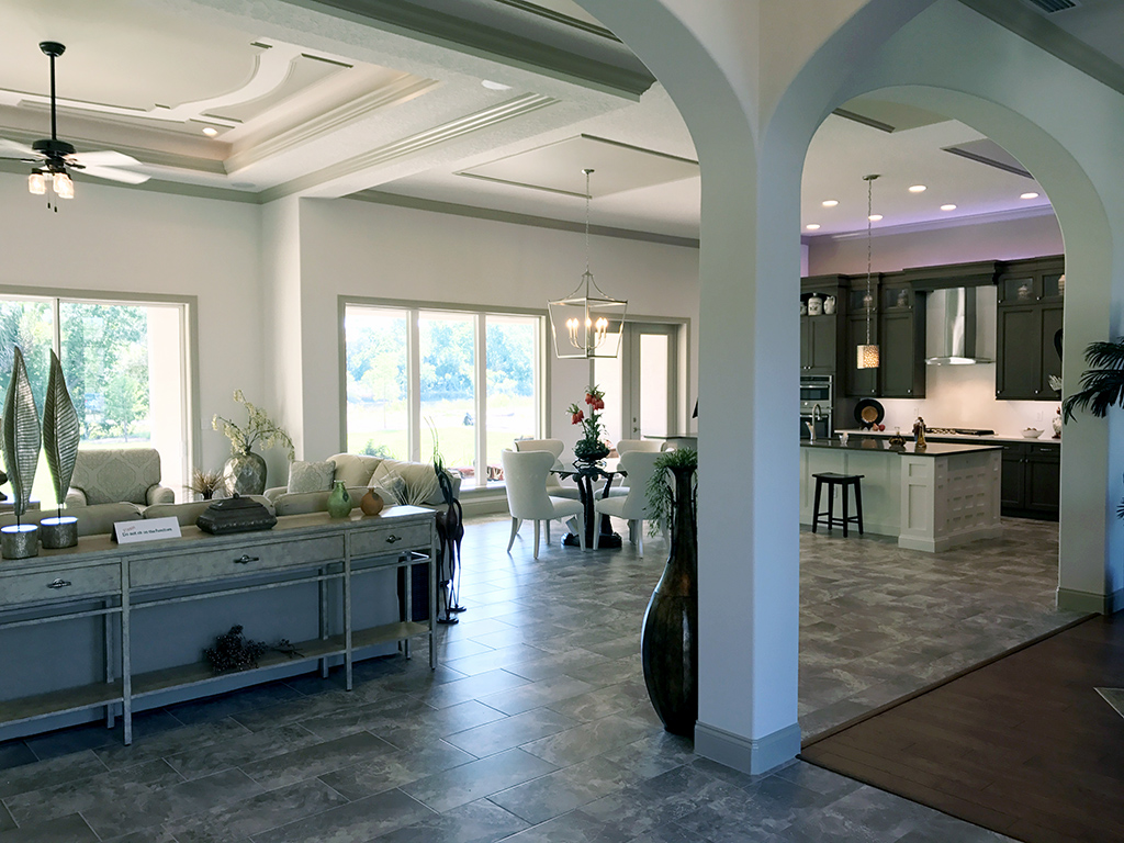 arched entry ways in an open floor plan including the kitchen, living room and large windows