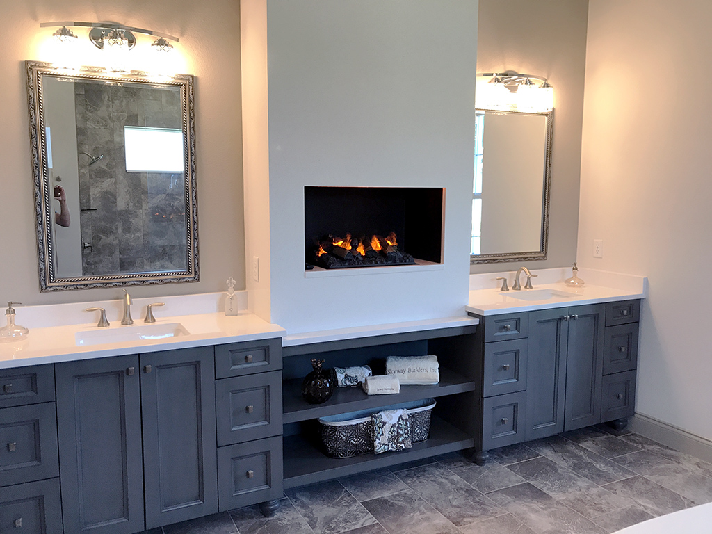 Master bathroom with double vanity separated by a gas fireplace