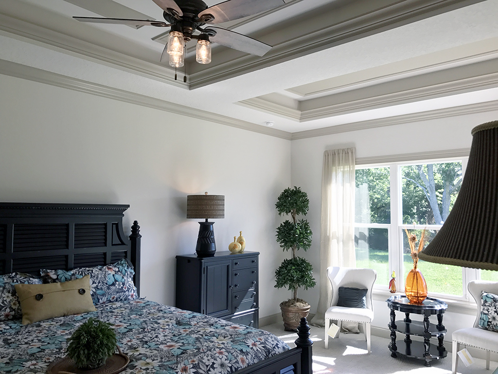 Fully furnished master bedroom with ceiling fan